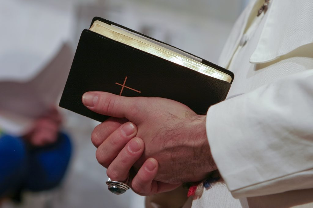 Man in popes garment holding holy bible.