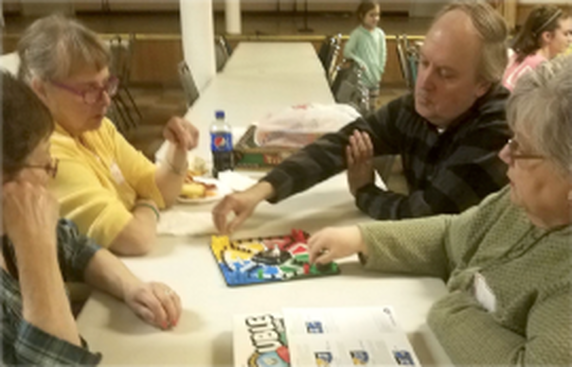 Four people playing the board game Trouble